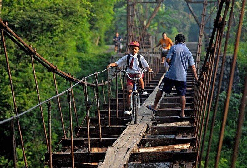 В ещё одной индонезийской деревне дети передвигаются на велосипедах над акведуком, разделяющим деревни Суро (Suro) и Племпунган (Plempungan) на острове Ява